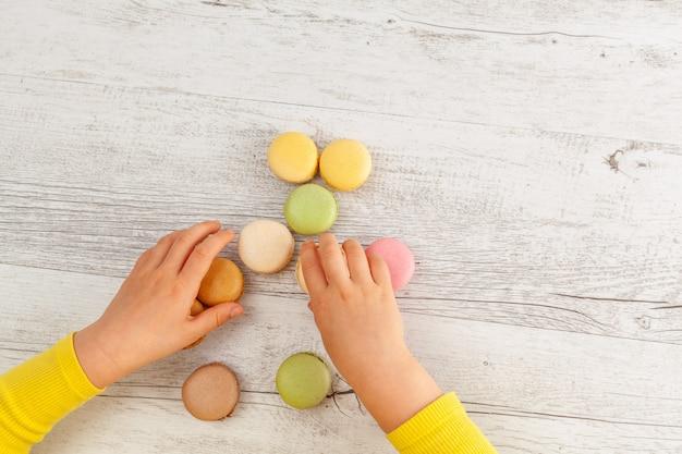 Mãos da menina com mangas amarelas, jogando com macarons na vista superior de mesa de madeira com espaço de cópia