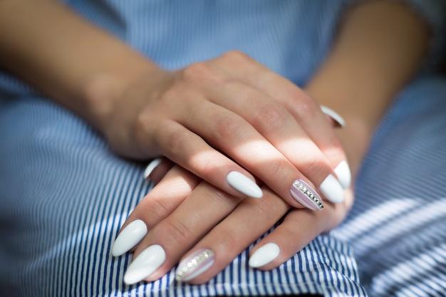 Mãos da menina com manicure de casamento