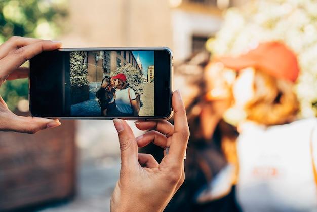 Mãos da menina tirando foto de duas mulheres se beijando em uma rua de madrid