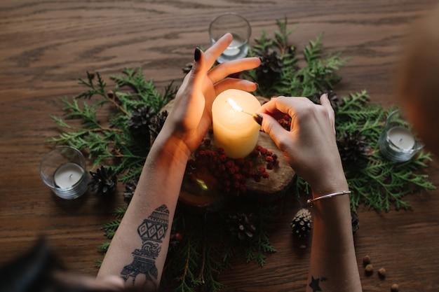Mãos da mulher acendendo uma vela