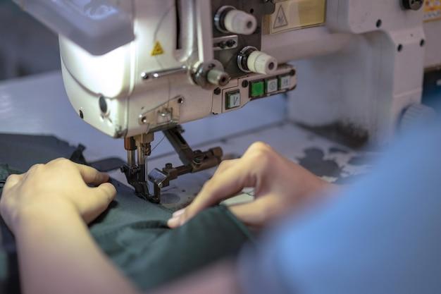 Mãos da mulher asiática nova que usa a máquina de costura na oficina.