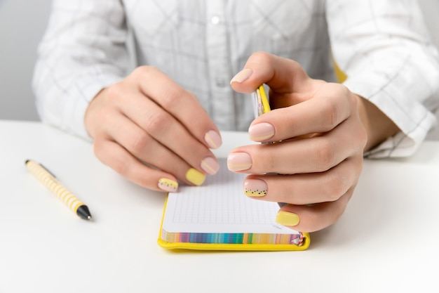Mãos da mulher bem cuidada segurando uma caneta e um bloco de notas. plano leigo, vista superior trabalhar no conceito de educação de escritório em casa.