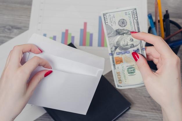 Mãos da mulher colocando dinheiro em envelope caderno gráficos papelaria mesa de madeira