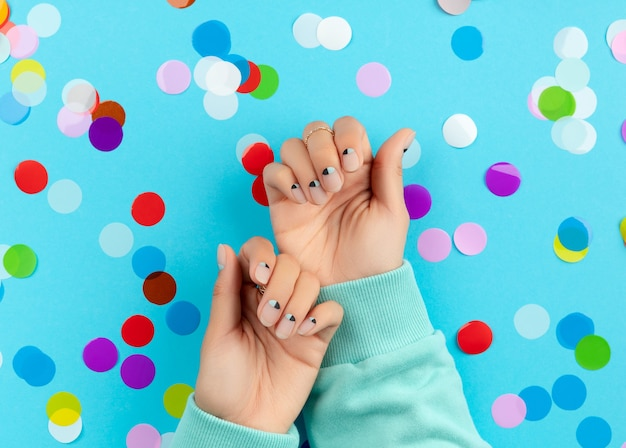 Mãos da mulher com confetes coloridos sobre fundo azul. conceito de salão de beleza, moda e spa
