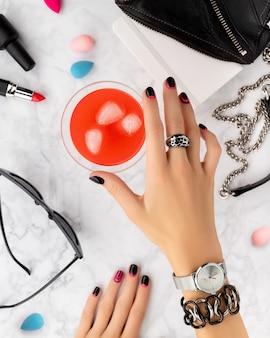 Mãos da mulher com manicure da moda segurando coquetel no mármore