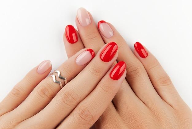 Mãos da mulher com manicure moderna vermelha sobre as tendências de design de manicure de parede branca