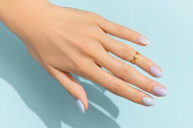 Mãos da mulher com manicure na moda na superfície azul. desenho de unhas de verão