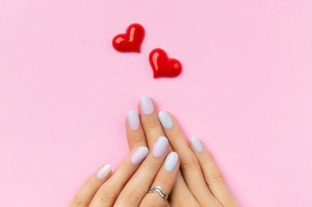 Mãos da mulher com manicure na moda na superfície rosa. desenho de unhas de verão