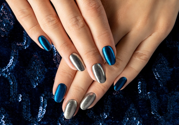 Mãos da mulher com manicure no fundo de brilho azul criativo. design de unhas de prata noite escura festa.