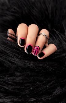 Mãos da mulher com manicure rosa e preta na moda com casaco de pele.