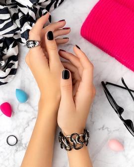 Mãos da mulher com manicure rosa e preta na moda.