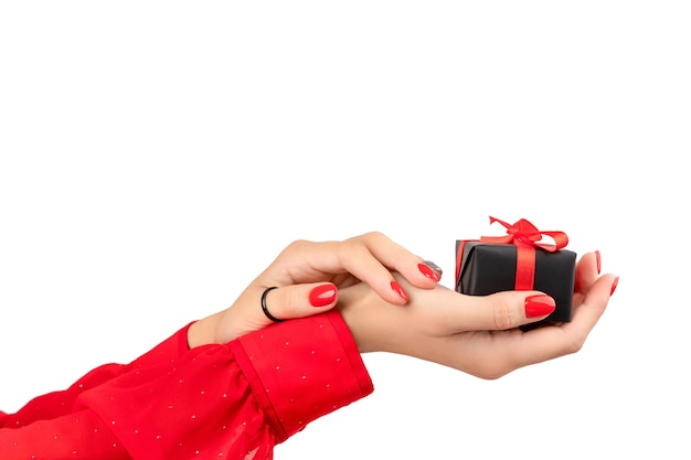 Mãos da mulher com manicure segurando um presente no fundo branco com espaço de cópia