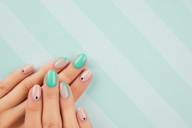 Mãos da mulher com manicure turquesa na moda com espaço de cópia. tendências de design de manicure de verão. conceito de moda beleza