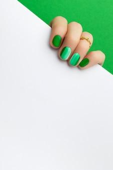 Mãos da mulher com manicure verde da moda segurando cartão postal