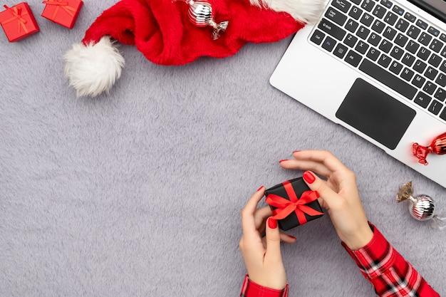 Mãos da mulher com manicure vermelha da moda segurando um presente