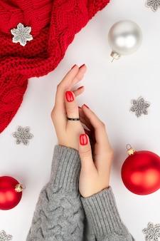 Mãos da mulher com manicure vermelha na moda.