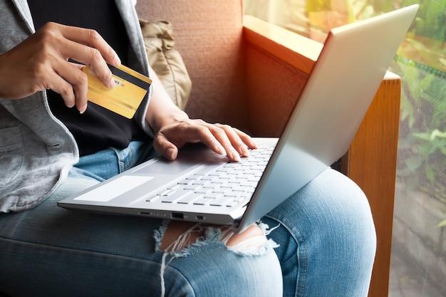 Mãos da mulher com portátil e cartão de crédito que compram em linha.