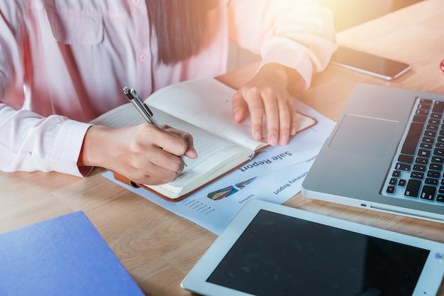 Mãos da mulher de negócio com o caderno da escrita da pena no fim da tabela da mesa de escritório acima. conceito de negócios.