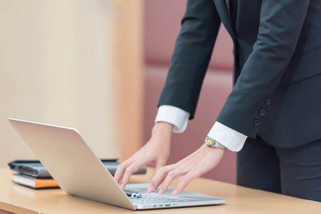 Mãos da mulher de negócios que datilografam no teclado do portátil na mesa.