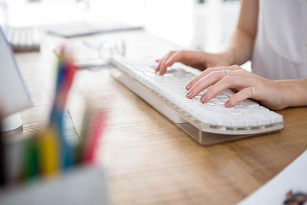 Mãos da mulher, digitando em um teclado em um escritório