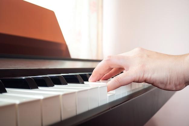 Mãos da mulher do close up que jogam o piano. música e arte de fundo.