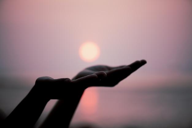 Mãos da mulher do close up que rezam abençoando do deus durante o fundo do por do sol.