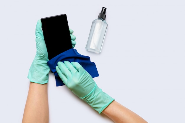 Mãos da mulher em luvas de látex, limpando o telefone móvel com vista superior do agente de descontaminação de álcool sobre fundo cinza claro
