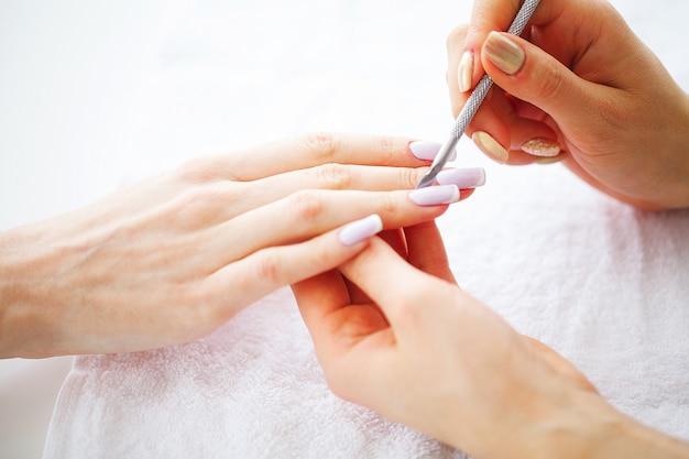 Mãos da mulher em um salão de beleza recebendo um procedimento de manicure. manicure spa