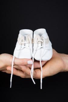 Mãos da mulher holdong sapatos pequenos para um bebê. waitong lovong parents