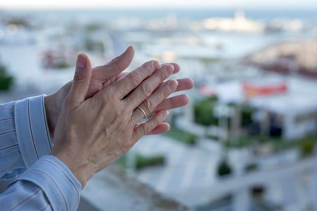 Mãos da mulher na varanda para aplaudir a equipe médica pela luta contra o coronavírus