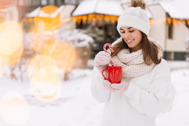 Mãos da mulher nas luvas que guardam uma caneca acolhedor com cacau, chá ou café quente e um bastão de doces.