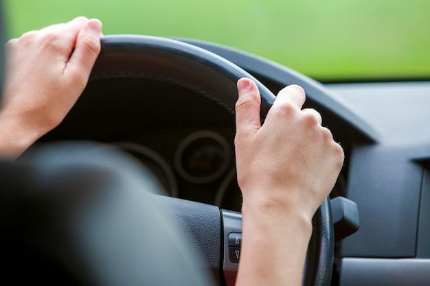 Mãos da mulher no volante que conduz um carro.