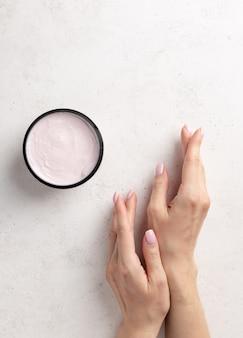 Mãos da mulher preparada com uma delicada manicure rosa e creme jar em um fundo de pedra branca minimalismo cuidados com a pele