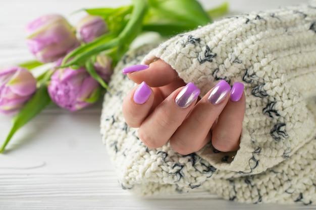 Mãos da mulher preparado com verniz de unha roxo, manicure, cuidados com a mão
