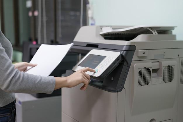 Mãos da mulher pressionando o fundo da impressora.
