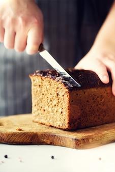 Mãos da mulher que cortam o pão recentemente suportado.