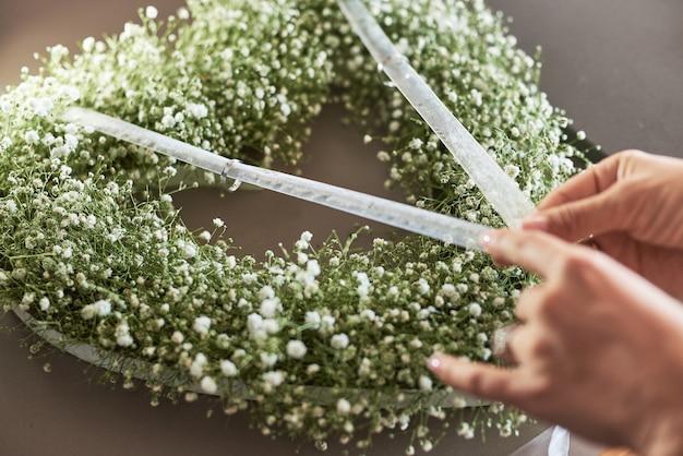 Mãos da mulher que fazem a composição da flor com alianças de casamento em uma forma de um coração.