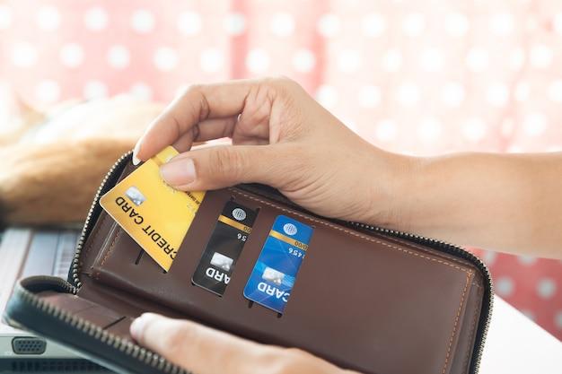 Mãos da mulher que guardam a bolsa e que escolhem o cartão de crédito. conceito de pagamento de e-business