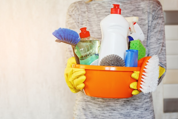 Mãos da mulher que guardam a cuba com fontes de limpeza.