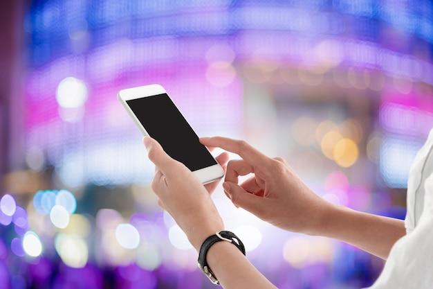 Mãos da mulher que guardam e que usam o smartphone com a tela vazia para seu texto ou propaganda isolada no fundo borrado.