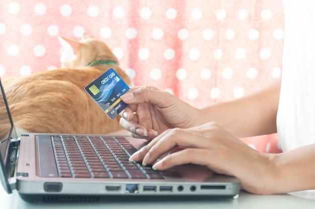Mãos da mulher que guardam o cartão de crédito plástico e que usam o portátil. conceito de compras e estilo de vida