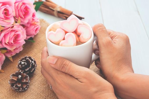 Mãos da mulher que guardam o chocolate quente com os marshmallows cor-de-rosa da forma do coração. conceito de amor