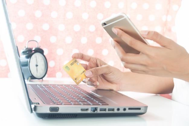 Mãos da mulher que guardam o telefone celular e o cartão de crédito plástico. e-pagamento. compras online