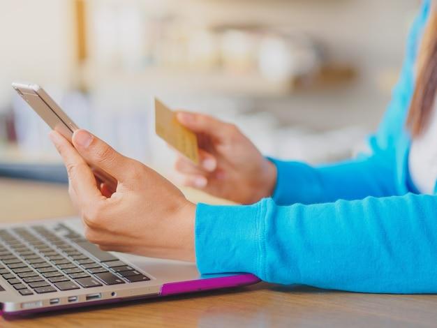 Mãos da mulher que guardam um cartão de crédito e que usam o smartphone e o laptop.