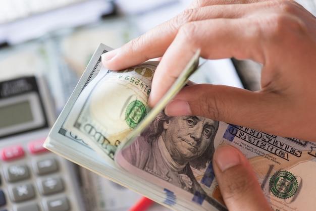 Mãos da mulher que guardaram e que contam o grupo de cédulas dos dólares de américa.