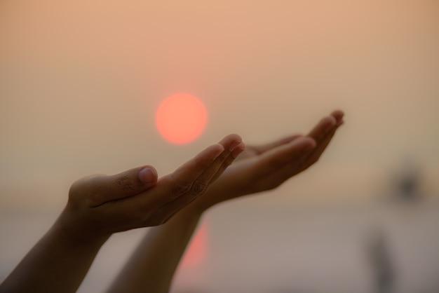 Mãos da mulher que rezam abençoando do deus durante o fundo do por do sol. conceito de esperança.