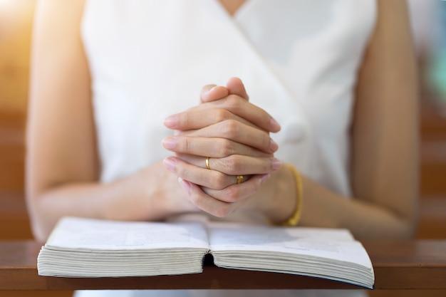 Mãos da mulher que rezam em uma bíblia sagrada na igreja para o conceito da fé, a espiritualidade e a religião cristã.