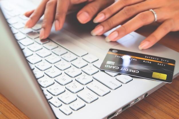 Mãos da mulher usando o laptop com o cartão de crédito plástico no teclado.