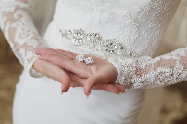 Mãos da noiva com jóias delicadas.