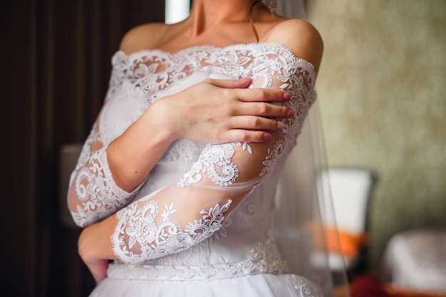 Mãos da noiva com uma manicure de casamento nas unhas